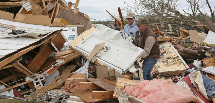 Roman Brown (left) and Sam Crawford search through the wreckage of a home in Hamilton, Miss., Sunday for a friend's lost medication.