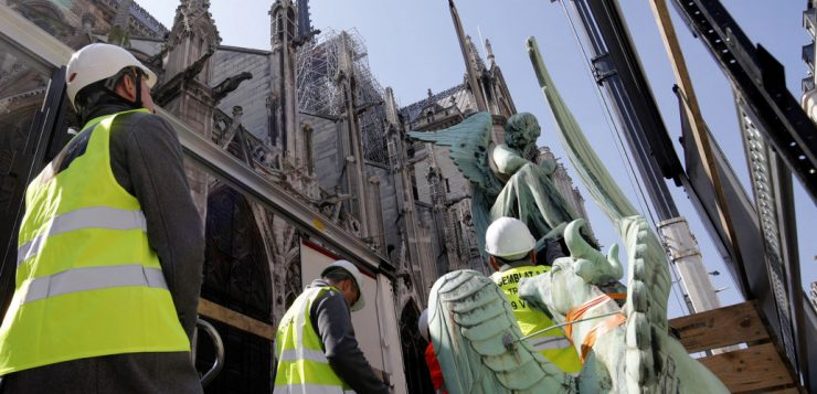 Statues are removed from the spire of Notre Dame Cathedral in Paris by a crane.