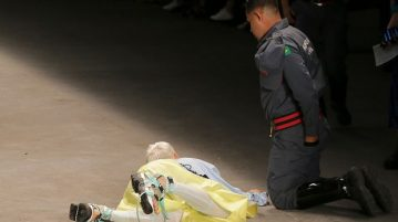 Tales Soares lies on the catwalk as a paramedic tends to him after his collapse.